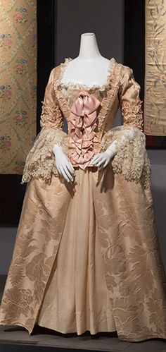 This gown is a Robe a l'anglaise, which translates to the dress of the English. The dress is composed of a panier to widen the hips, a corset to make the waste appear thinner, and a stomacher that is attached on the front of the bodice. http://sites.fitnyc.edu/depts/museum/Retrospective/18-Century-3.html