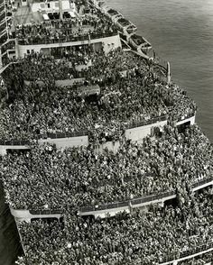 """This is one of our favorite WWII photos. Taken in 1945, it shows thousands of troops pulling in to NY Harbor aboard the Queen Elizabeth. If this was 2016, there would be thousands of family members there waiting, but back in 1945, train travel was expensive and arrival ships (and dates) often changed. So after they got off the boat, they'd get a train ticket then go to Western Union to send a """"I'm back - see you Tuesday!"""" telegram."""