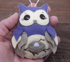 **NO LONGER ACCEPTING CUSTOM ORDERS OR ORDERS FOR PERSONALIZATION** This cutesy little owl was hand stitched and embroidered using dark dusty purple, buttery yellow, and taupe wool blend felt.  Her tummy features a little egg in a nest perched on the branch of a tree, representing baby on the way.  A tiny heart and the year 2016 are hand stamped on an aluminum tag that adorns the back of the ornament.  Lightly stuffed with polyfill and finished with a loop of cotton cord for hanging…