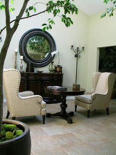 Some of my favorite things - wingbacks, round black mirror and giant potted tree - all arranged in such an inviting way!
