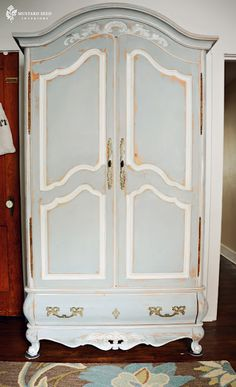 The armoire is painted in a mix of equal parts Louis Blue and Paris Gray with Annie Sloan's Chalk Paint.  The detail is painted in Old White. at Miss Mustard Seed blog.