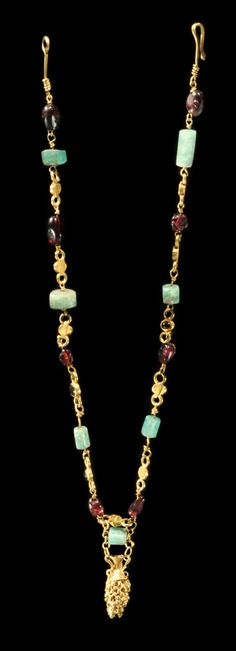 Roman gold, emerald, and garnet necklace. With a gold granulated pendant in the form of an amphora. 3rd Century AD