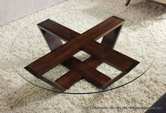 Otro modelo de mesa de centro con patas de madera y sobre de vidrio.