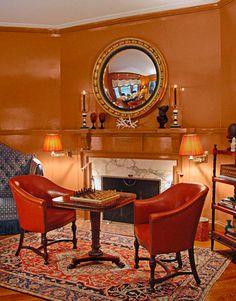 Orange living room: Painted mantle + round mirror