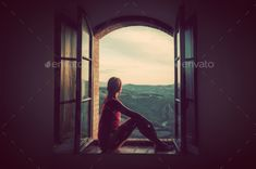 Young woman sitting in an open old window looking on the landscape of Tuscany, Italy. by photocreo. Young woman sitting in an open old window looking on the landscape of Tuscany, Italy. Conceptual romantic, dreaming, ...