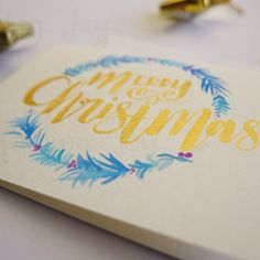 """A hand-painted Christmas card featuring """"Merry Christmas"""" in gold ink and a hand-painted blue and purple feathered Christmas wreath."""