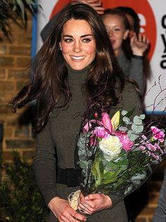 "Looking effortlessly chic in a Ralph Lauren dress, the Duchess of Cambridge accepts a floral bouquet after a Tuesday evening visit with husband William"" to homeless charity Centrepoint in London."