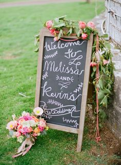 chalkboard wedding sign with flowers, photo by Lauren Fair Photography http://ruffledblog.com/stonebrook-farms-bohemian-wedding #weddingsigns #signage
