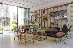 En una estantería de madera reciclada (Net Muebles) se exhiben barcos de madera (Sarmiento) y obras realizadas por la dueña de casa. En el living, sofá oscuro, lámpara de pie con pantalla cobre, sillón BKF de piel, sillas bajas 'Museo' y mesa de lapacho 'Bandeja' (todo de Net Muebles) con ramas verd.  /Pompi Gutnisky