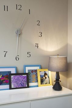 How to curate Kids' Art 7 (by www.houzz.com): In a similar vein, these works are clustered along a dresser. Bright frames add extra punch. Combining them with vibrant works is effective and eye catching in a neutral setting
