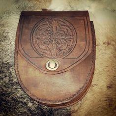Pouch feito em couro, com costura e marcação manual.
