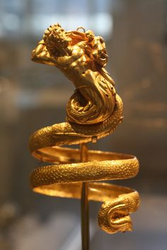Male Triton Gold Armband Greek, Hellenisticca, 200B.C. This imposing serpentine armband represents a male triton holding a small winged Eros. The hoops behind the tritons' head were used to attach the armband to the sleeves of a garment, for otherwise, its weight (over 61/2 ounces) would have caused them to slip down the arms. There is matching female triton armband that can be seen at the click-through link Photo by Brass Ivy Design, Object at the Metropolitan Museum of ...