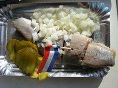 Traditional Dutch Food: Zoute haring met uitjes en zuur (raw salty herring with onions and pickles).