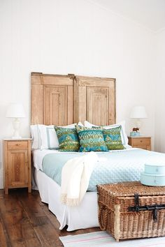 Antique doors create rustic headboard. Aqua & green accents, cozy throw, delicate bedside table lamps, pasted striped rug , blue hat boxes soften wood. Wicker trunk at foot of bed perfect place for luggage in guest room (swap these cushions for blue and white striped)