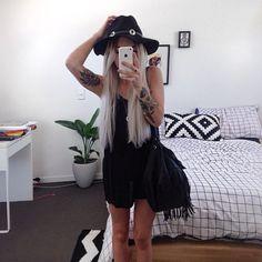 Black singlet dress, felt hat, and fringe bag