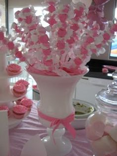 LOVE this idea as a center piece or an element on a candy buffet! Salt water taffy in the color of your choice on skewers in the container of your choice!! A little floral foam and either tulle or more of the same or contrasting candy to fill the container and cover your work... VOILA!!
