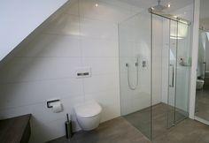 Die vom Purismus inspirierte, reduzierte Gestaltung ist für das Bad mit Dachschräge von Vorteil, weil es größer wirkt und den Bauherren mehr Bewegungsfreiheit einräumt