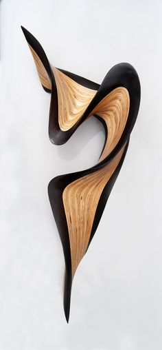 Wenge Jive by Kerry Vesper. This wood sculpture ripples across the wall with a flourish. The artist hand cuts layers of Baltic birch and *wenge wood*, then meticulously stacks and glues them together before carving and sanding them into the final form. The piece has a protective clear tung oil/urethane finish and has keyhole brackets for mounting. Can be hung in any orientation. Requires no maintenance.