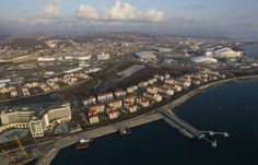 An aerial view from a helicopter shows the Olympic Park under construction and the Olympic Village in the Adler district of the Black Sea re...