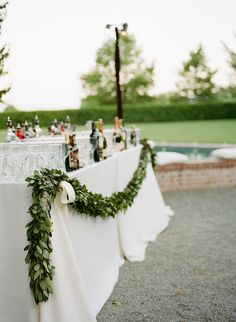 Garlands of ruscus will be draped across the front of each bar, tied with gold ribbons on each end.
