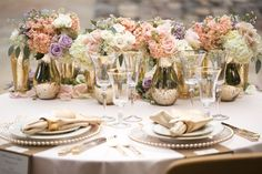 Lavender and blush pink roses, white hydrangeas. Floral garlands for the reception tables and sweetheart table. Gold mercury glass vases. Gold and cream lines.