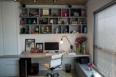 Escritório na sala com bancada e estante