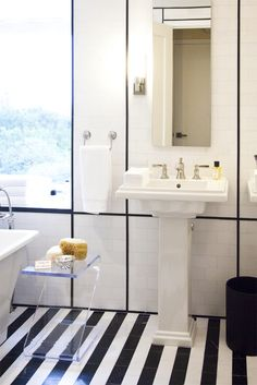classic black and white bath with modern touches.  floor to ceiling subway tile with black linear detailing, updated pedestal sink, acrylic side table, narrow mirror, and black and white striped floors.