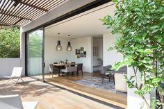 חלונות גדולים מחברים בין החצר לפנים, וכשהם פתוחים מתרחב שטח האירוח המשפחתי אל הדק המוצל  (צילום: עמית גרון)