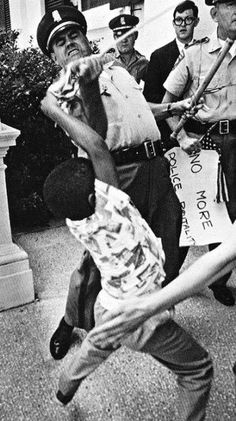 """An Ironic & Iconic Image from the Civil Rights Movement....A Young Man has his American Flag ripped out of his hands by a White Policeman. He earlier had his """"No More Police Brutality"""" sign Confiscated - Jackson Ms (1965) Photo By Matt Heron"""