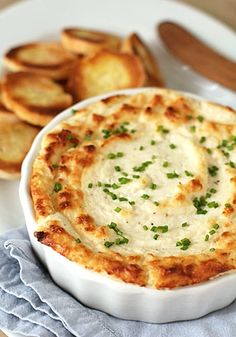Hot Onion and Cheese Soufflé Dip    serves 10-12    1 large sweet onion, chopped  3 (8-ounce) packages of cream cheese, softened  2 cups freshly grated parmesan cheese  1/2 cup mayonnaise  1/2 teaspoon cayenne pepper, plus more to taste  1/4 cup finely chopped fresh chives, plus more for garnish  Kosher salt and freshly ground black pepper    Preh