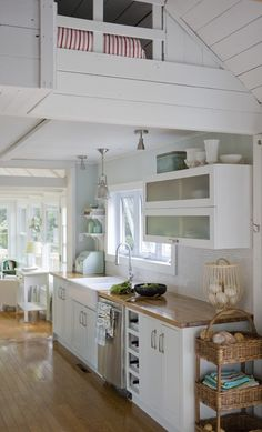 The narrow kitchen of this Laurentians, Que. cottage seems wider because of the white cupboards, simple backsplash and uncluttered storage. Views to the lush surroundings can be enjoyed while washing dishes.