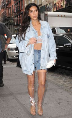 Kim Kardashian in an oversize denim jacket, bra top, jean shorts and clear denim thigh-high boots