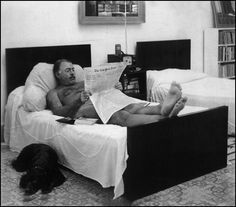 Ernest Hemingway reading The New York Times in bed, naked – can't cover as much with an iPad; By his side, surprisingly, a dog. Photograph by George Leavens.