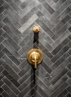 Grey Chevron Soapstone Tiles & Unlacquered Brass Shower Valves.