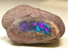 Ópalo en bruto, destellos violetas y azules.