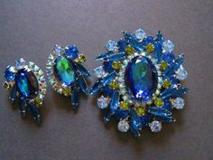 This Juliana DeLizza & Elster brooch and earrings demi-parure features watermelon or heliotrope stones with flashes of green, blue and purple accented by teal, aurora borealis, light blue and peridot/