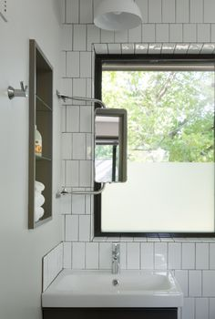 Zilker Hideaway : Rick & Cindy Black Architects, photo by Whit Preston. Trucker mirror for the visitor on the go. Subway tiles in a vertical stagger & Alabaster Sconce from Schoolhouse Electric.