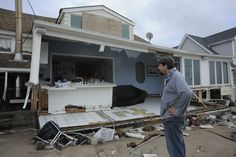 Ian Fischer of Center Moriches surveys the damage to the rear of his home where he lived with his parents. Sandy caused the Moriches Bay to flood nearby homes. (Oct. 30, 2012) Photo Credit: John Roca