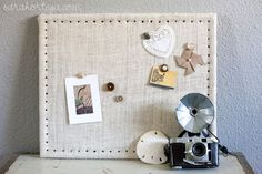 Burlap Cork Board    What you'll need:  - cork board  - fabric (burlap or whatever you like.)  - upholstery tacks (found at Jo Ann Fabrics)  - scissors  - staple gun  - hammer