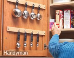 Free up drawer space by hanging measuring cups inside a kitchen cabinet. Position and mount a wood strip so that the cups will hang between the shelves and allow the door to close completely. Mount a second strip for your measuring spoons, then screw in cup hooks on both strips.