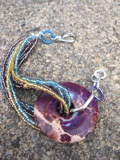 Beaded Jewelry. Now this is what I call a statement bracelet! A bright purple gemstone with turquoise, gold, and purple seed beads! Great with Jeans and a Tee! Check out the link for more color options and matching necklaces! Winter colors now on sale! 50% off the regular price of $29!