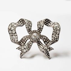 An antique bow-shaped brooch composed of gold, silver and old cut diamonds, circa 1880s. The 3 main stones weigh ~2 to 3 carats. These jewels were made for the French nobility at the time.