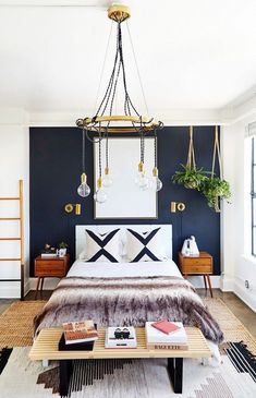 Glam bedroom with a black contrast wall, a chandelier, and layered rugs #LampBedroom