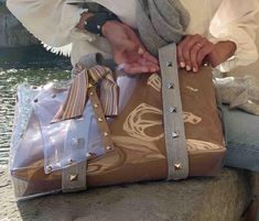 """Giulia Leoni on Instagram: """"Sitting by the Arno river... wearing Grey Strap Bag with Sand liner, Limited Edition Missoni clutch and Camo Ribbon Cuff... what a…"""" Clear Tote Bags, Arno, Missoni, Suitcase, Ribbon, River, Group, Board, How To Wear"""