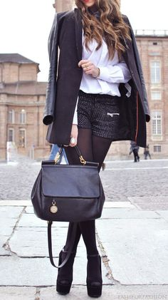 Black coat, white shirt, black boucle textured shorts, bag and booties