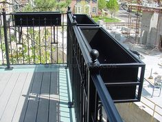 fabricated steel flower box hanging on a balcony railing.