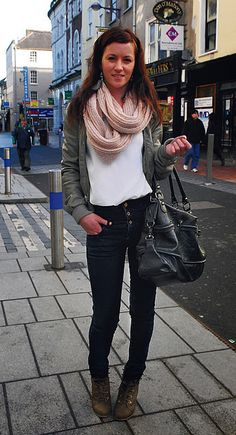 Army green jacket, pink infinity scarf, dark jeans, boots.