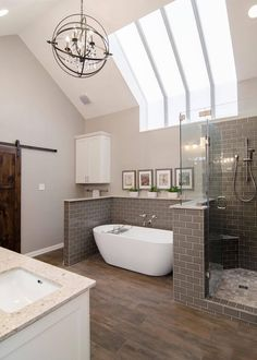 This beautiful spa bathroom combines unique details—like the orb-shaped chandelier and vertical skylight stripes—with classic elements for a refreshing, relaxing space. Gray tile smartly wraps around the shower and soaking tub; wide-plank wood floors and Bathroom Renos, Modern Master Bathroom, Bathroom Cabinets Diy, Bathroom Makeover, Small Bathroom Layout, Bathroom Interior, Modern Bathroom, Amazing Bathrooms, Bathroom Decor