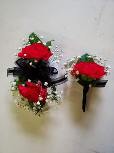 Red Carnations, baby's breath, and greens with black trim on a wrist corsage and boutonniere. Corsage And Boutonniere, Boutonnieres, Brownwood Tx, Red Carnation, Wrist Corsage, Local Florist, Baby's Breath, Corsages, Flower Delivery