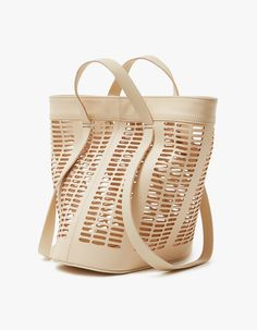 From Modern Weaving, a basket tote in Neutral. Main compartment with clasp closure. Shoulder straps. Carrying handles. Tonal stitching. Die cut detailing. Structured base with embossed logo.   • Leather • Made in USA